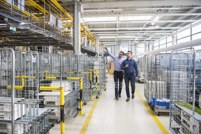 Men walking in factory — Stock Photo