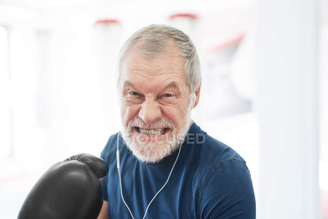 Aggressive senior man with earphones — Stock Photo