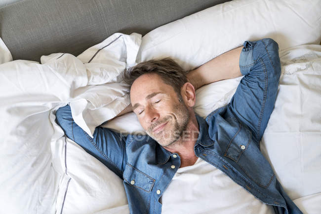 Man lying on bed with eyes closed — Stock Photo