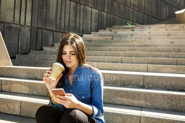 Femme assise sur les escaliers avec café à emporter — Photo de stock