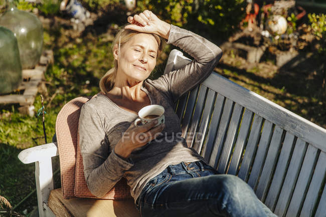 Woman relaxing on garden bench — Stock Photo