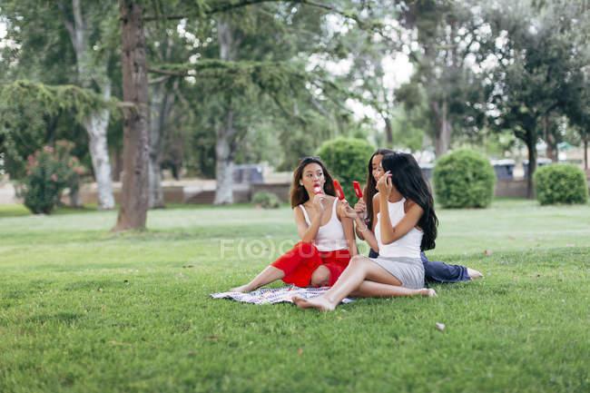 Друзья, есть фруктовое мороженое в парке — стоковое фото