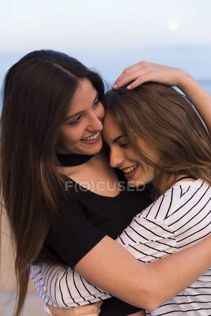 Young women standing at seaside — Stock Photo