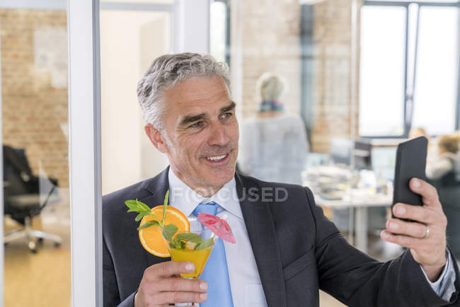 Businessman drinking cocktail — Stock Photo