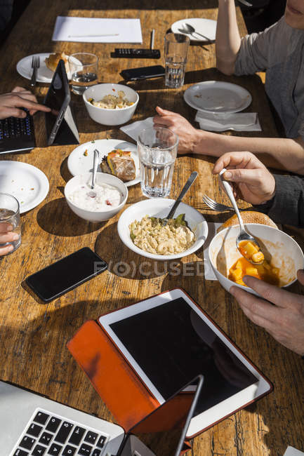 Colleagues having lunch together in the office, partial view — Stock Photo