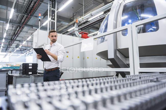 Человек делает заметки на фабрике — стоковое фото
