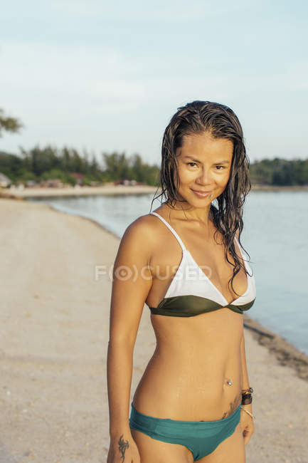 Усміхається жінка, стоячи на пляжі — стокове фото