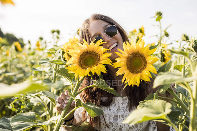 Woman standing in sunflower field — Stock Photo