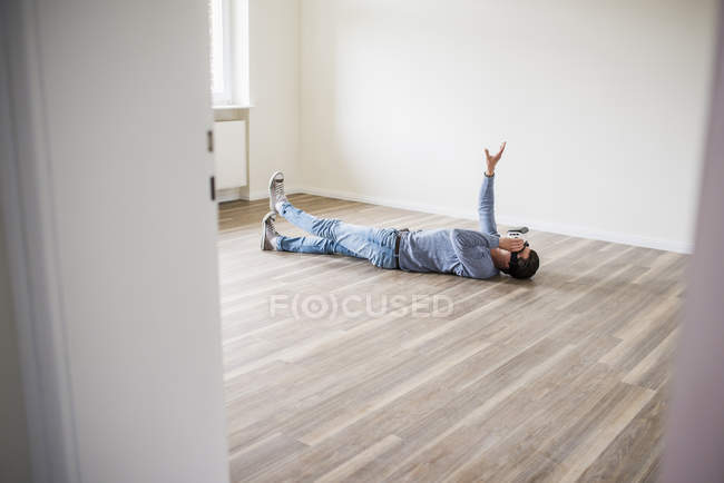 Man lying on the floor in empty apartment wearing virtual reality glasses — Stock Photo
