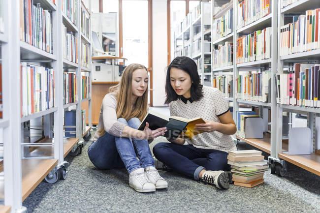 Двох дівчат-підлітків сидячи на підлозі в публічній бібліотеці і читати книгу — стокове фото