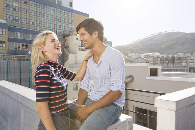 Young couple laughing on rooftop — Stock Photo