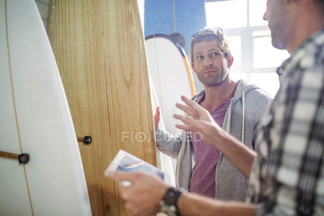Продавец, объясняя о доски для серфинга — стоковое фото