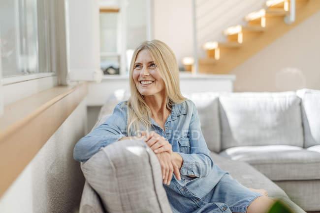Lächelnde Frau auf der Couch — Stockfoto