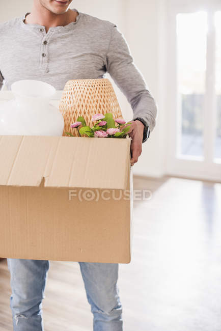 Cropped view of young man carrying cardboard box in new home — Stock Photo