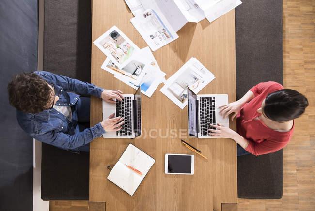 Мужчина и женщина с ноутбуками — стоковое фото