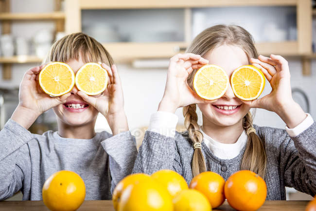 Brother and sister covering eyes with oranges — Stock Photo