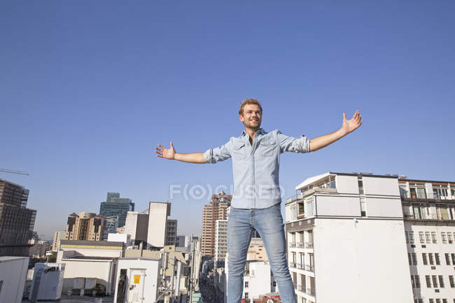 Young man standing on rooftop terrace — Stock Photo