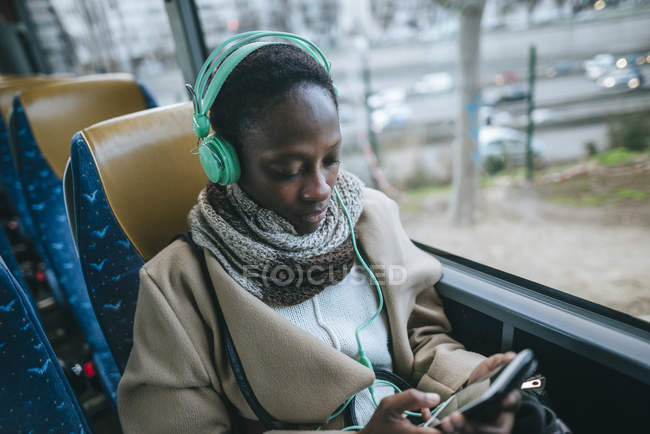 Young woman in a bus listening music — Stock Photo