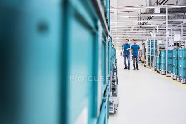 Men walking in industrial hall — Stock Photo