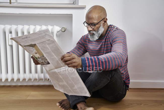 Mann am Boden sitzen und Zeitung lesen — Stockfoto