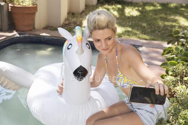 Woman taking selfie with unicorn — Stock Photo