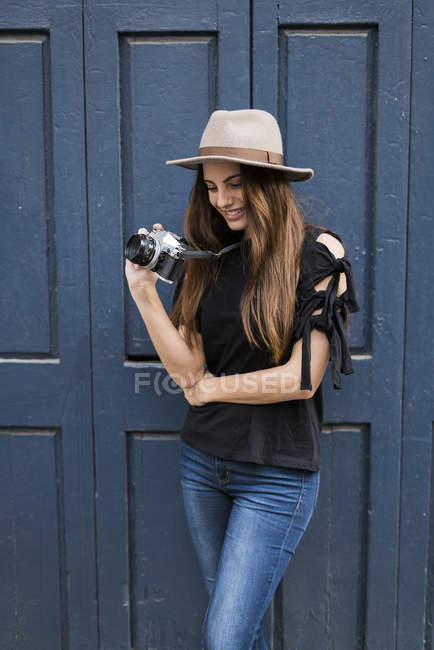 Женщина с фотоаппаратом, стоящая у двери — стоковое фото