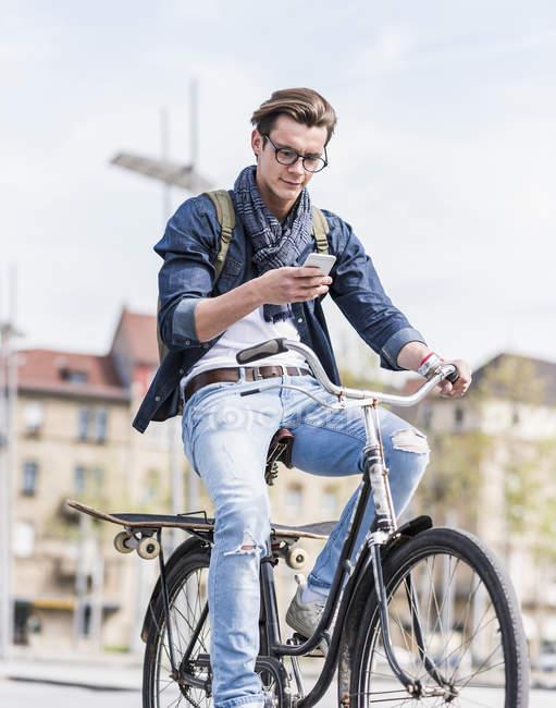 Homem andar de bicicleta e usando telefone — Fotografia de Stock