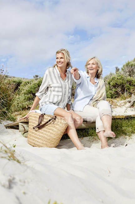 Madre e hija sentadas en la playa - foto de stock