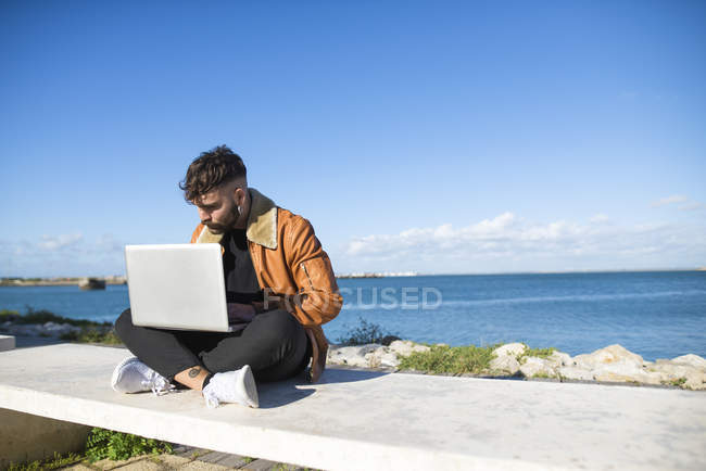 Man at the harbor using laptop — Stock Photo