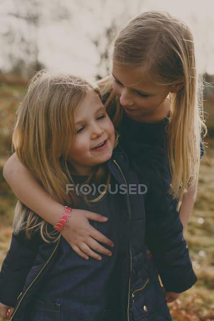 Girl hugging sister — Stock Photo
