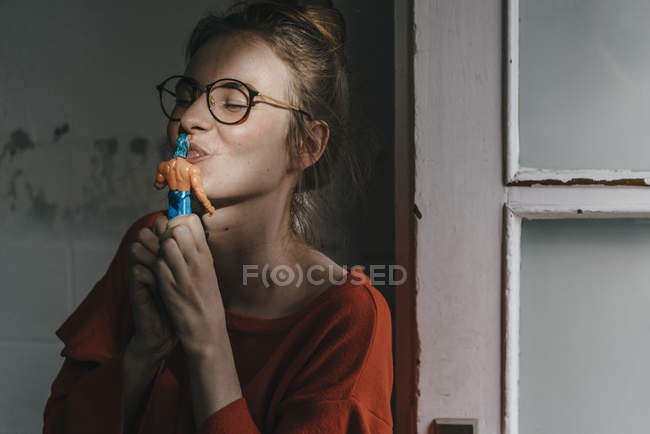 Woman kissing superhero comic figurine — Stock Photo