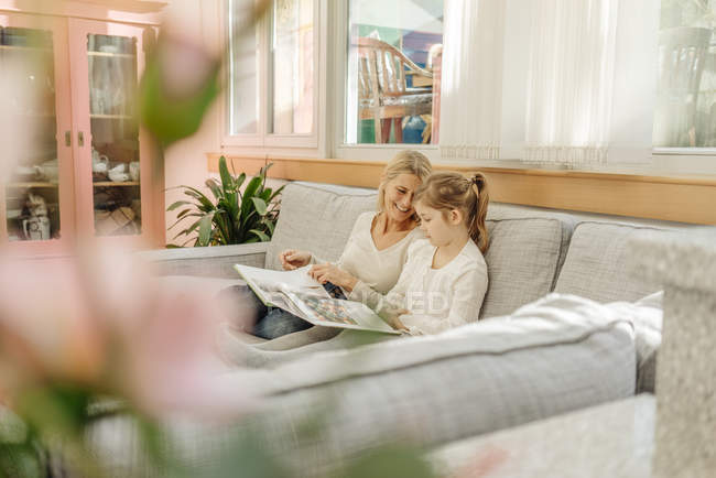 Woman and girl watching photo album — Stock Photo