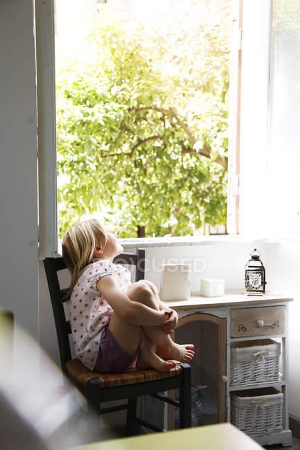 Дівчина сидить на стільці в вікно — стокове фото