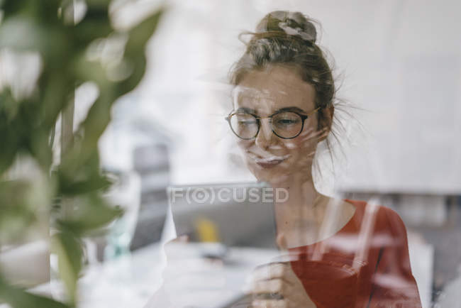 Woman using tablet behind glass pane — Stock Photo