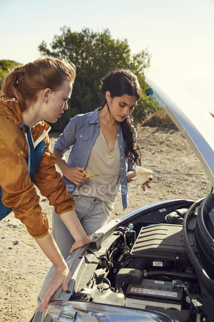 Mujeres revisando el coche de pie en la carretera - foto de stock