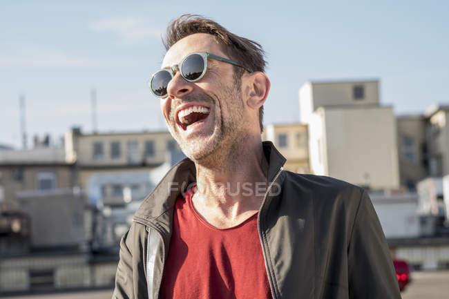 Uomo con stoppia indossando occhiali da sole — Foto stock