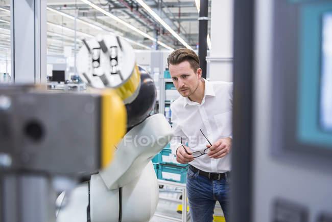 Man examining assembly robot — Stock Photo