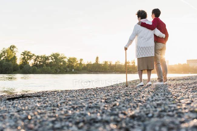 Seniorin steht mit erwachsener Tochter am Strand — Stockfoto