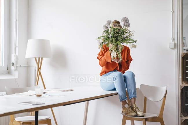 Woman sitting on table holding flower vase — Stock Photo