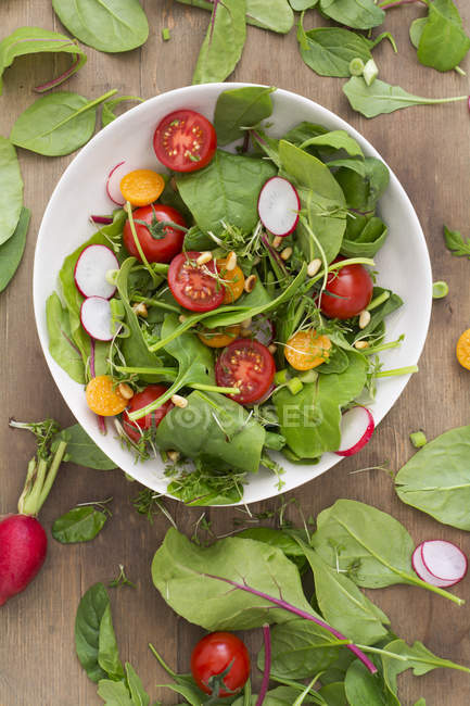 Schüssel mit gemischtem Salat auf Holztisch — Stockfoto