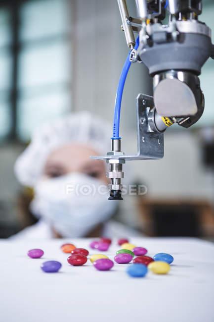 Roboterhandling Süßigkeiten mit Frau im Hintergrund — Stockfoto