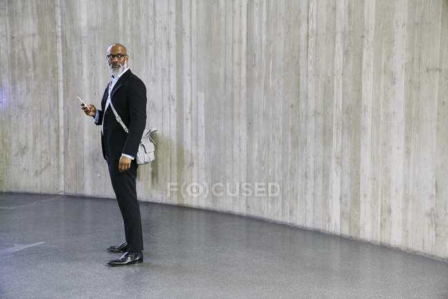 Businessman with bag using smartphone — Stock Photo