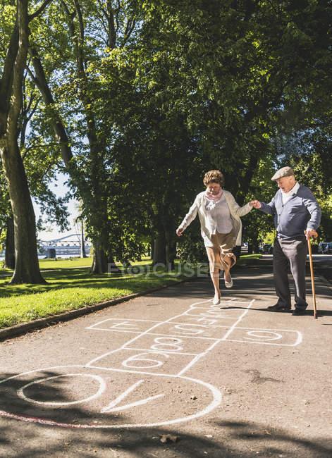 Donna anziana giocare hopscotch mentre il marito — Foto stock