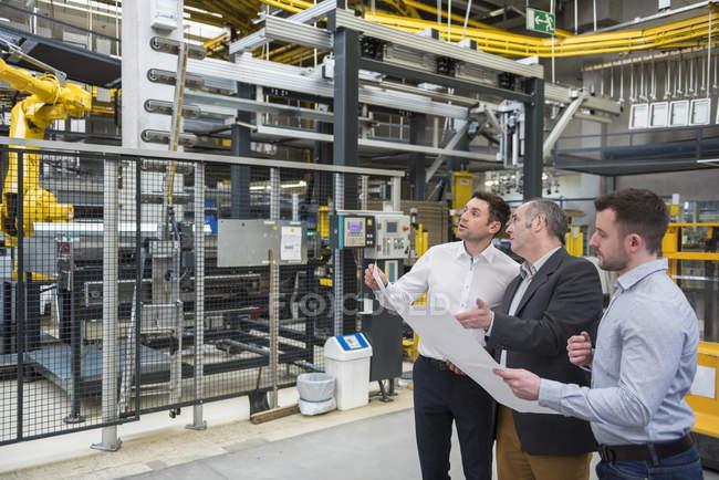 Homens com planta falando na fábrica — Fotografia de Stock