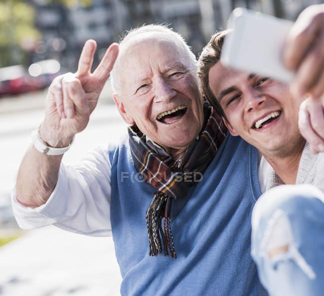 Senior man and adult grandson taking selfie — Stock Photo