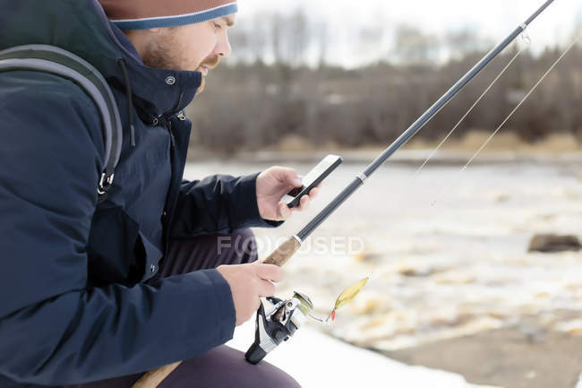 Man fishing looking at cell phone — Stock Photo