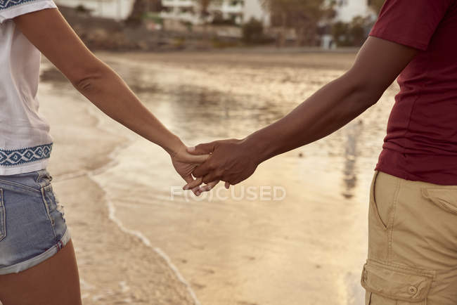 Couple in love holding hands on the beach on the beach, close-up — Stock Photo