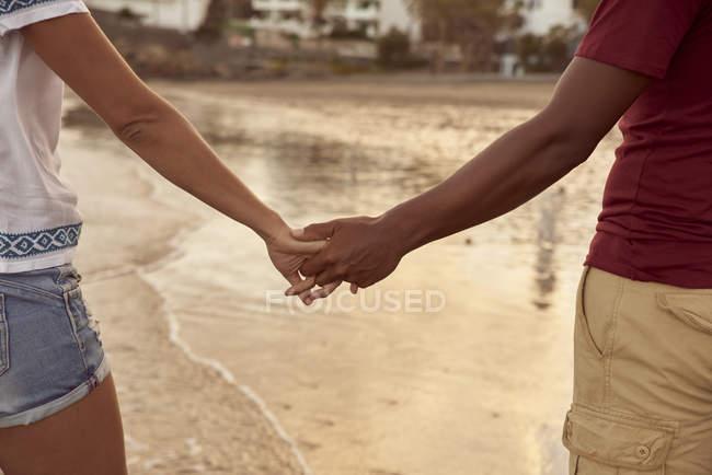 Pareja de enamorados cogidos de la mano en la playa en la playa, primer plano - foto de stock
