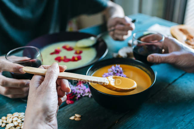 Hand of woman eating creamed pumpkin soup — Stock Photo