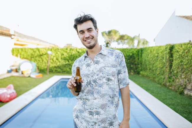 Man drinking beer at poolside — Stock Photo